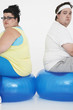 Unhappy overweight man and woman sitting back to back on exercise balls, portrait