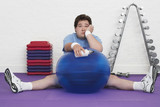 Overweight Man sitting on floor with exercise ball in health club, portrait