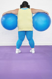 Overweight Woman Holding two Exercise Balls, back view