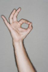 Man making okay sign, arm raised, close up on hand