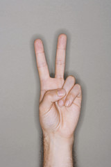Man making victory sign, close-up on hand