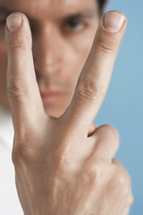 Man holding up two fingers, close-up