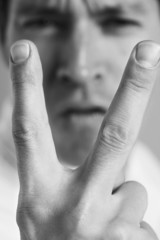 Man holding up two fingers, close-up, black and white