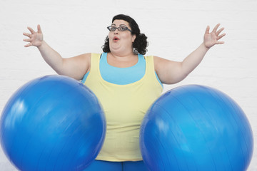 Overweight Woman dropping two Exercise Balls