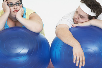 Disinterested overweight man and woman lying on Exercise Balls, close up