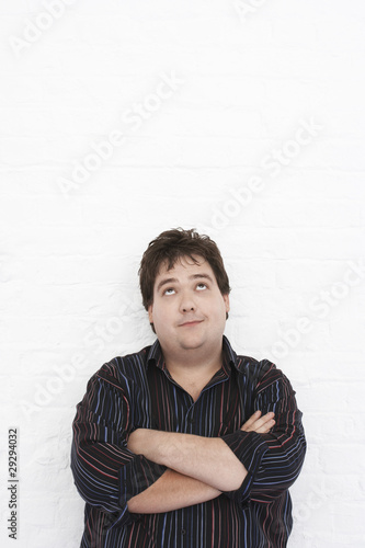 Man standing against wall with Arms Crossed looking upwards, portrait