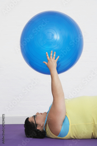 Overweight Woman lying down Holding up Exercise Ball