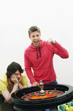 Young man celebrating at roulette wheel while friend loses, portrait