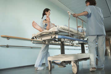 Nurses Moving Patient on gurney in hospital Corridor, low angle view