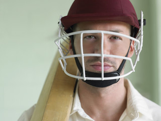 Cricket player wearing helmet and holding bat, close-up, portrait