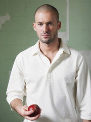 Cricket player holding ball, portrait