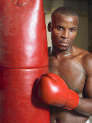 Boxer holding punching bag, portrait