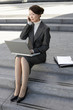 Businesswoman on outdoor Steps, Using Laptop and talking on mobile