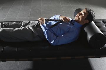 Businessman Lying on Sofa, adjusting tie