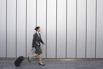 Businesswoman walking outdoors, pulling suitcase behind her, side view