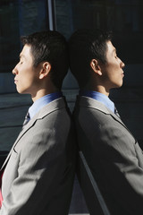 Businessman Leaning Against reflective Wall outside, profile