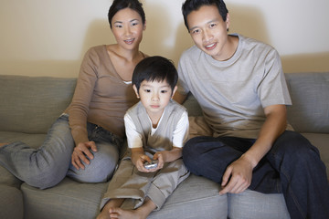 Couple sitting on sofa, Watching Television while son is using remote control