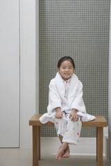 Young Girl wearing bathrobe, Sitting on Bench by Bathtub