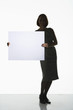 Silhouetted woman standing, holding large blank card to side