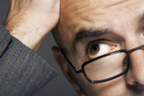 Balding businessman wearing glasses, hand on head, close up
