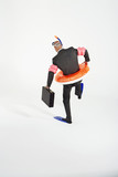 Middle-aged businessman in flippers, inflatable rubber ring, snorkel and goggles waddling, carrying briefcase, back view