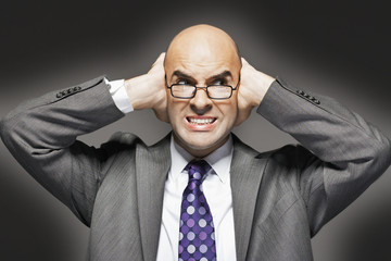Bald businessman holding hand over ears, looking sideways, making a face