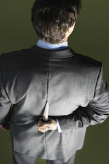 Mid-adult businessman standing, holding knife behind back, back view