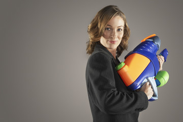 Smiling businesswoman standing, holding water gun, side view
