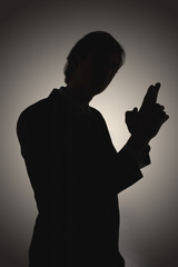 Shadow of man making gun-shaped gesture, side view