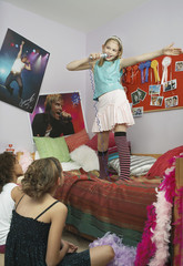 Girl standing on bed singing, friends watching from floor
