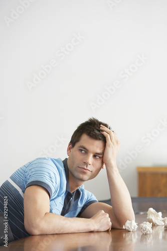Frustrated Man sitting at conference table With Crumpled Paper looking over shoulder, side view