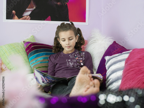 Barefoot Young Girl Reading Magazine, reclining on bed with many pillows