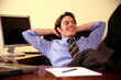 Young businessman relaxing with hands behind head