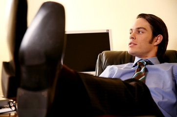 Young businessman sitting with feet on desk