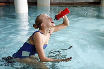 Young woman on exercise bike in spa pool