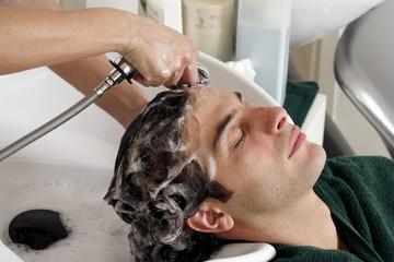Young man having his hair  washed at a salon
