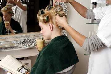 Young woman sitting under  hairdryer