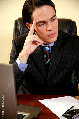 Young businessman sitting at desk and thinking