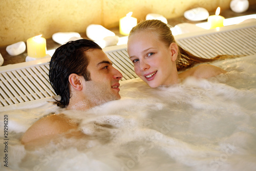 One man with two woman  in jacuzzi at a spa