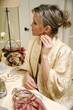 Woman sitting at the dressing table and putting in ear ring