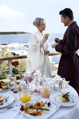 Mature couple having breakfast on hotel terrace