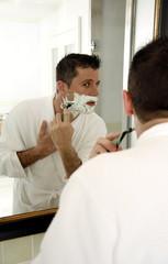 Man shaving in front of mirror