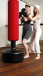 Student and teacher practicing a basic move on the punching bag