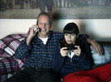 Grandfather and granddaughter watching television