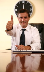 Businessman sitting at desk and  making a thumbs up gesture
