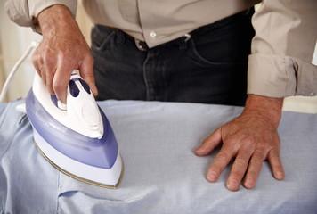 Mature man ironing shirt