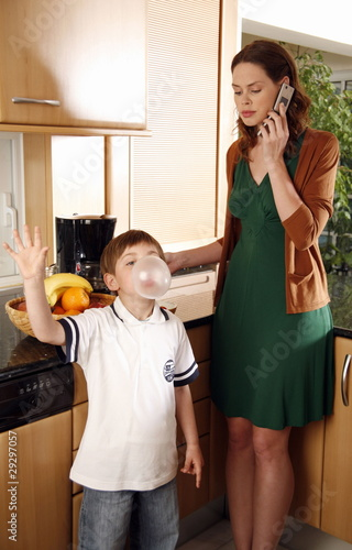 Woman talking on cell phone and boy doing bubble with gum in the kitchen