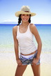 Young woman on beach in tank;hat;and shorts