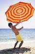 Man on beach with beach umbrella