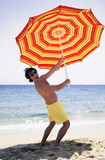 Man on beach with beach umbrella
